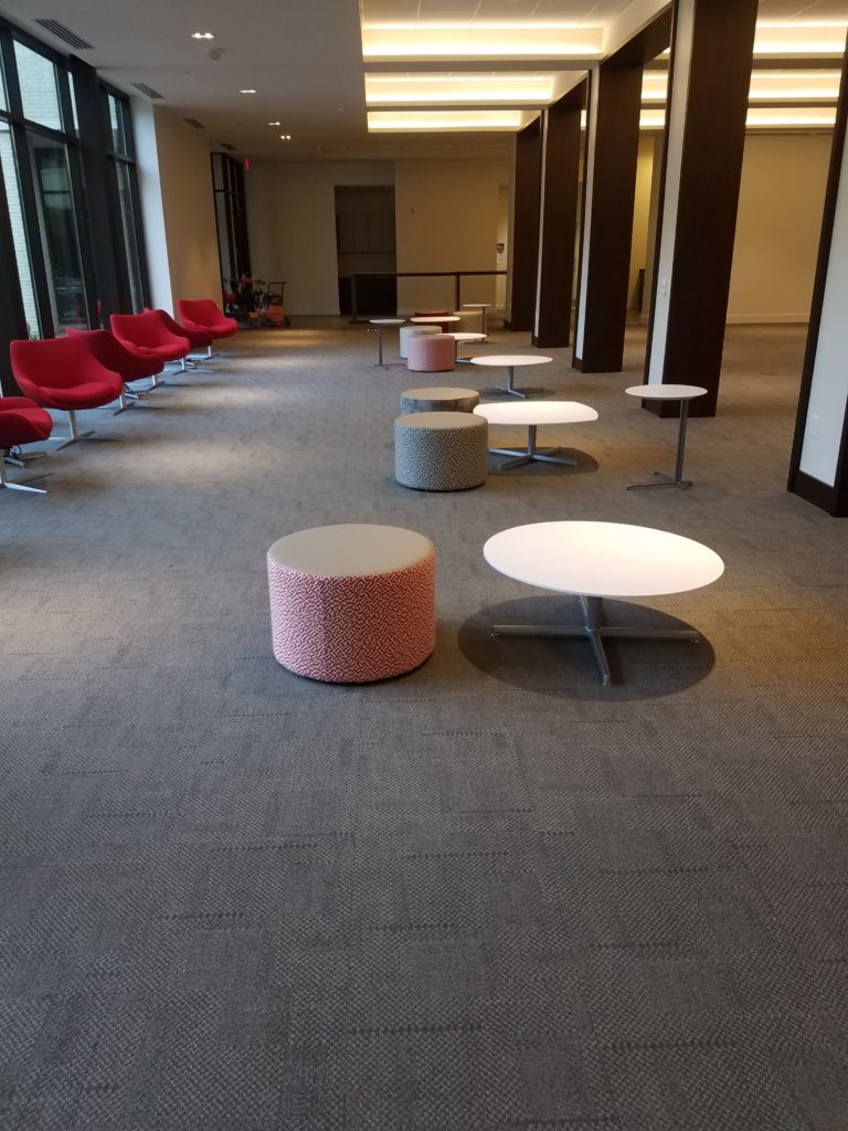 soft red chairs near a glass wall; round ottomans and low tables on carpet